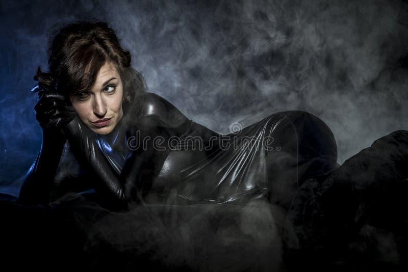 Framtid den sexiga brunetten i svart latexdräkt, mode sköt av a royaltyfri fotografi