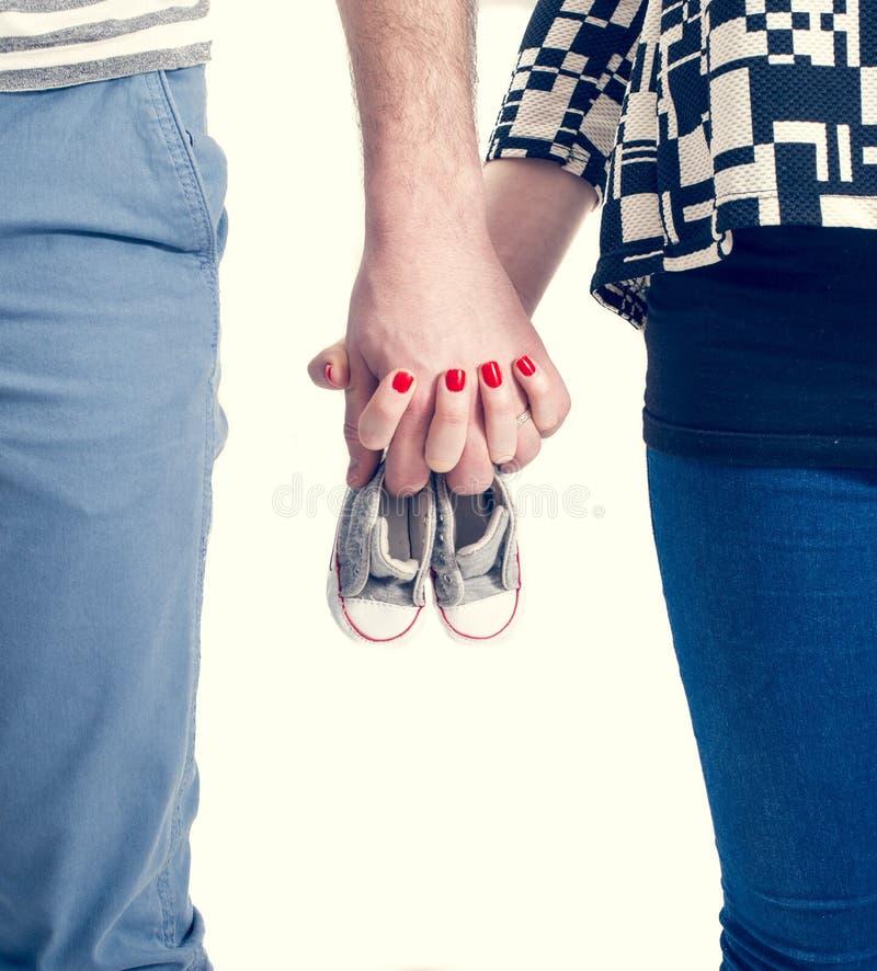 Framtid uppfostrar innehavhänder och ett par av små skor royaltyfri foto