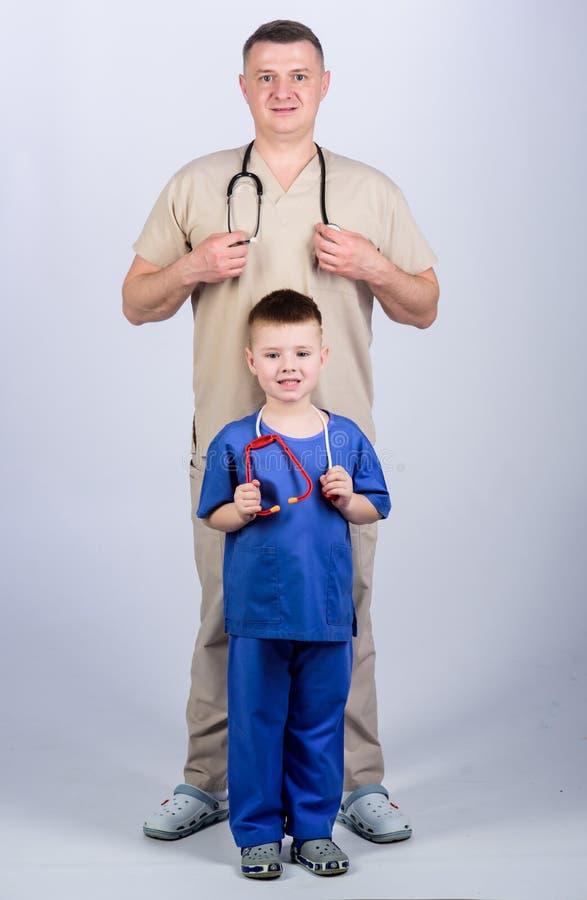 Framtida yrke Vill vara läkare som pappa Cute killlek Familjeläkare Pediatriska begrepp far royaltyfria bilder
