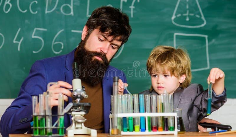 Framtiden av minnet fader och son på skola tillbaka skola till Förklaring av biologi till barnet Kemi och fysik royaltyfria foton
