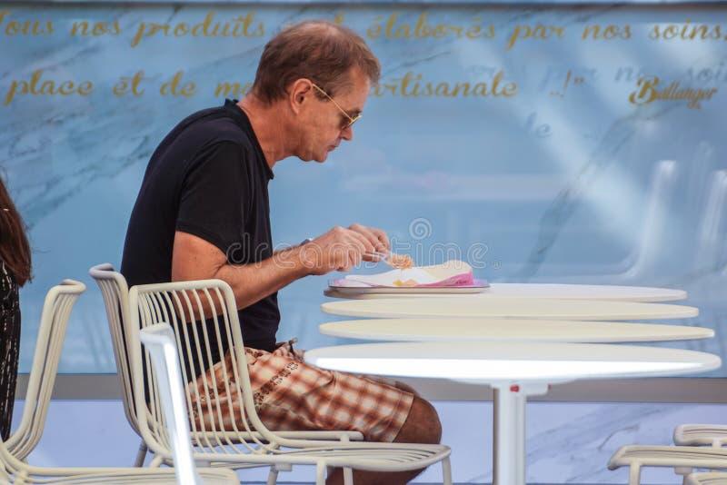 França, 16 de agosto de 2017 agradável: um homem não identificado come seu café da manhã que senta-se em um café no centro do tur fotografia de stock