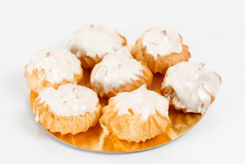 Francés tradicional Profiteroles, pasteles de los choux con crema azotada dentro Grupo de postre francés en el fondo blanco fotos de archivo