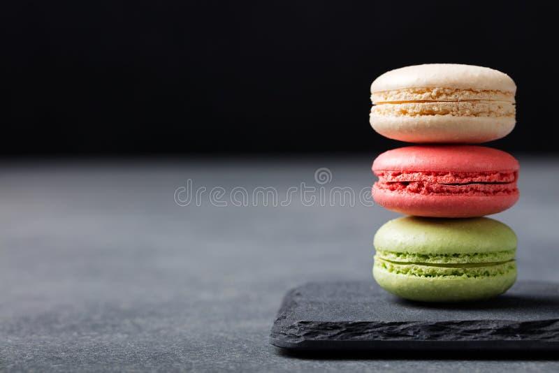 Francês colorido Macarons no espaço da cópia do fundo da pedra da ardósia imagem de stock