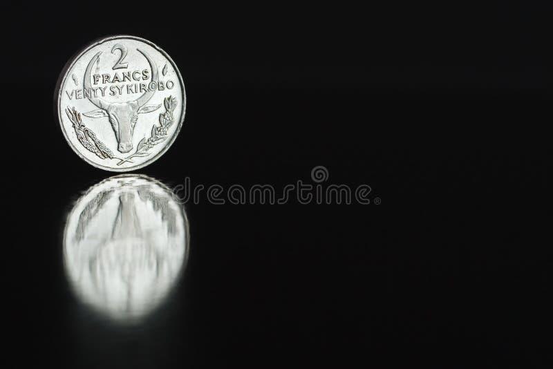 Franc malgache 1981 de la pièce de monnaie deux sur le bord sur le fond noir avec la réflexion images libres de droits