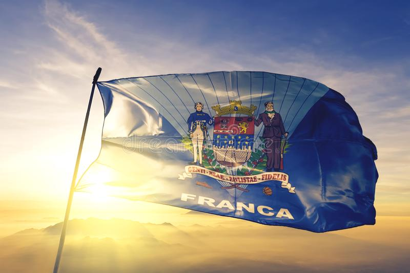 Franca of Brazil flag waving on the top sunrise mist fog. Franca of Brazil flag textile cloth fabric waving on the top sunrise mist fog royalty free stock images