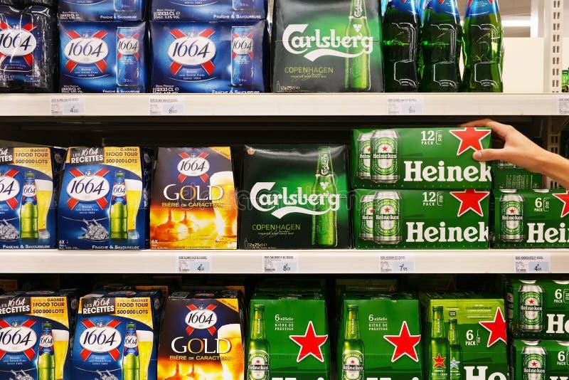 Beer packings in a Store. FRANCE - AUGUST 2017: Shelves with assortment of Kronenbourg 1664, Carlsberg, Heineken brand cardboard packings beer in a Super U stock image