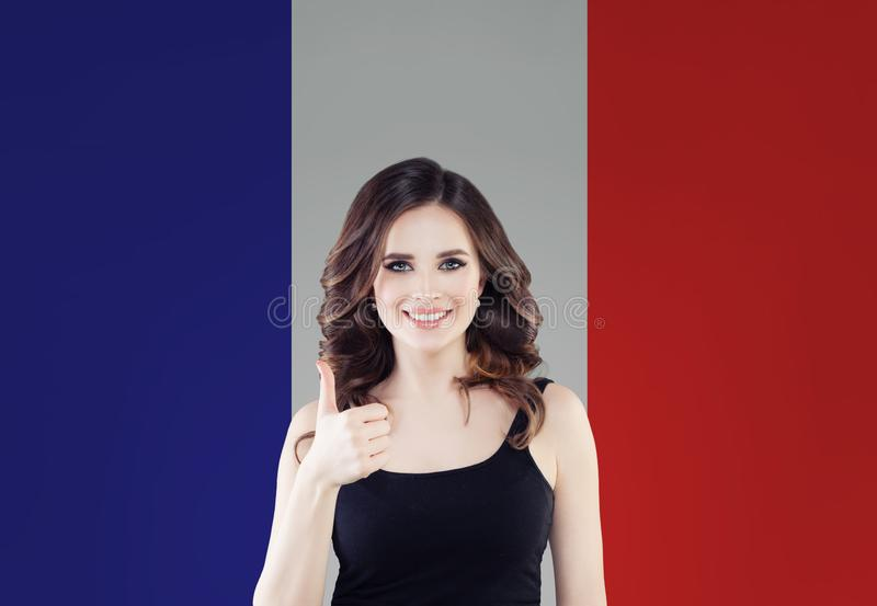 France concept with happy woman showing thumb up on French flag background. Travel in France and study french language stock photo