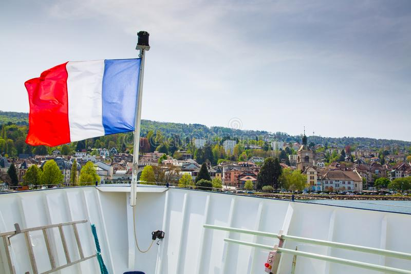 France flag on cruise ship in fron of Evian-les-Bains city in France. France flag on cruise ship in fron of Evian-les-Bains city, France stock photo