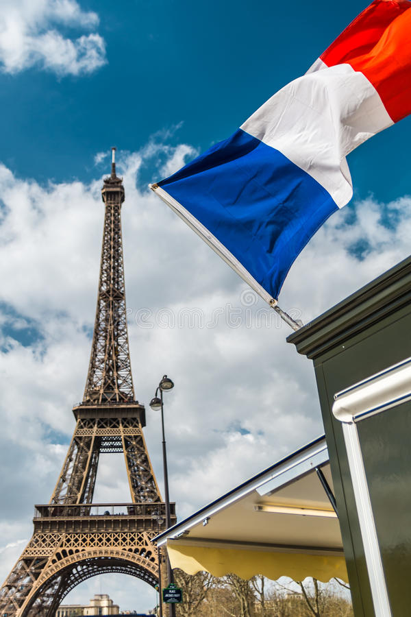 France flag over blue cloudy sky and Eiffel tower in Paris royalty free stock photo