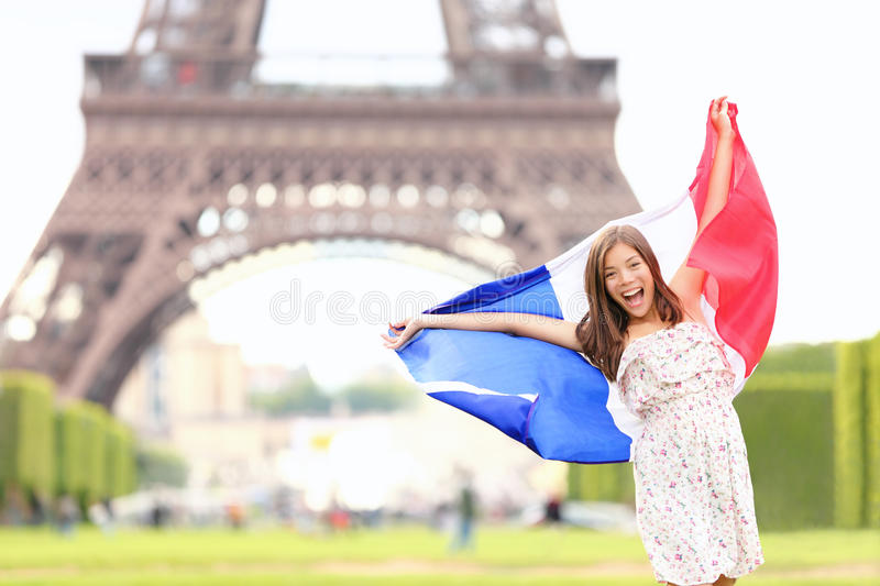 France - french flag woman by Eiffel tower, Paris. France travel concept with excited and happy young girl holding the French flag