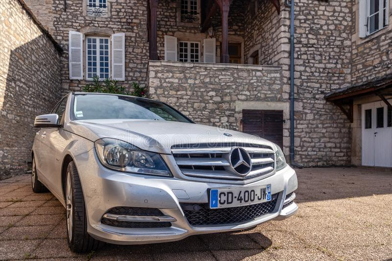 France Lyon 2019-06-20 closeup luxury silver German car sedan premium Mercedes C class with EU registration number near stone stock photo