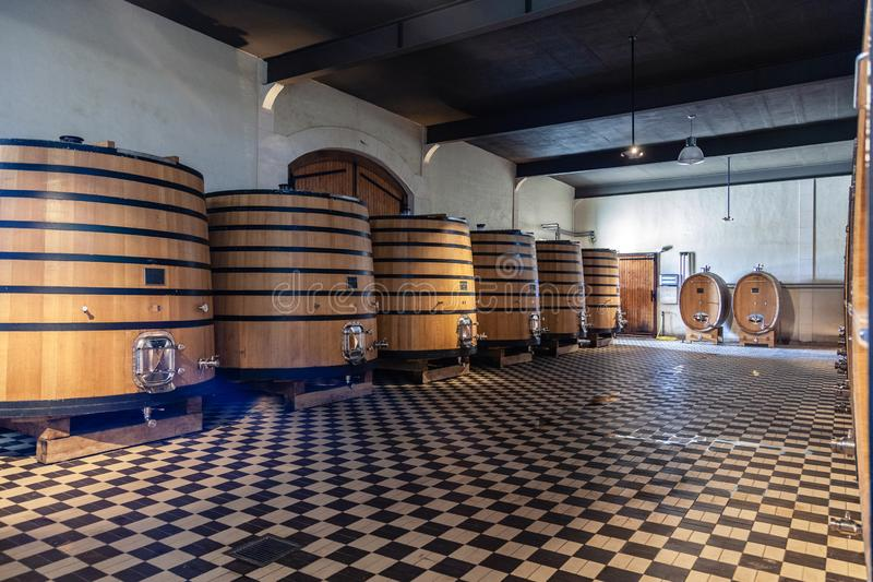 France Lyon 2019-06-21 stack of wooden barrels, aging, fermentation process, store in modern Brocard cellar, chess floor. Concept royalty free stock image