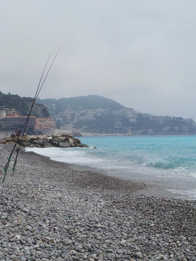 France Nice Cote d Azur pebbles beach sea waves fishing rid. France Nice Cote d Azur pebbles beach sea waves detail fishing rod royalty free stock photos