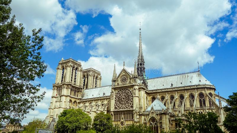 France Notre-Dame de Paris Cathedral in bright sunny day. Side view of France Notre-Dame de Paris Cathedral in bright sunny day clear blue sky royalty free stock images