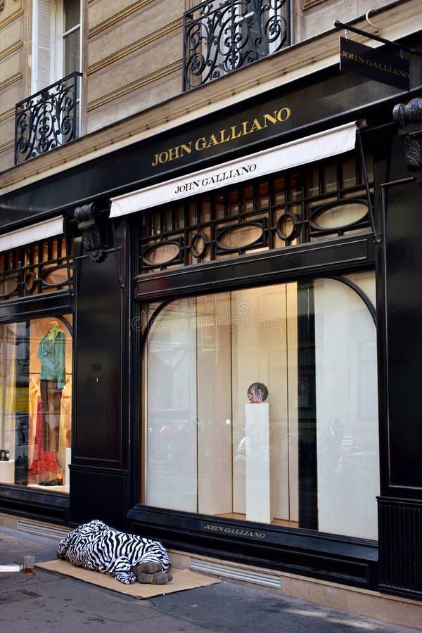 france paris En hemlös sover på lådor framme av en lyxig boutique på den Marais fjärdedelen arkivbilder