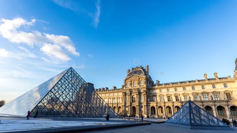 france paris Februari 2018: Louvremuseumsikt på solnedgången, med exponeringsglaset av de reflekterande molnen för pyramid royaltyfria bilder