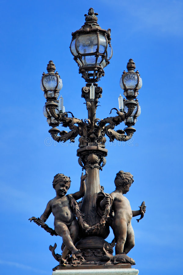 France, Paris: Old lamp-post. France, Paris:blue sky and a bronze old lamp-post with two nice sculpted figures stock photo
