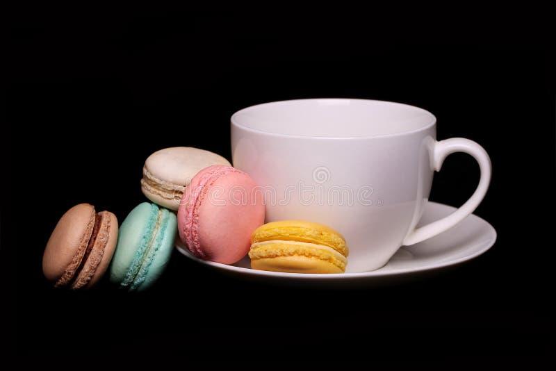 Francese variopinto Macarons con la tazza di tè sopra il nero fotografie stock libere da diritti