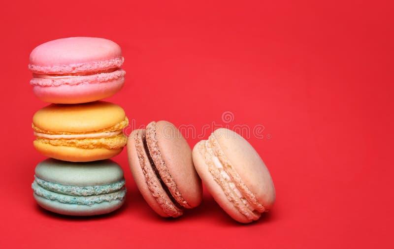 Francese variopinto Macarons sopra rosso fotografia stock libera da diritti