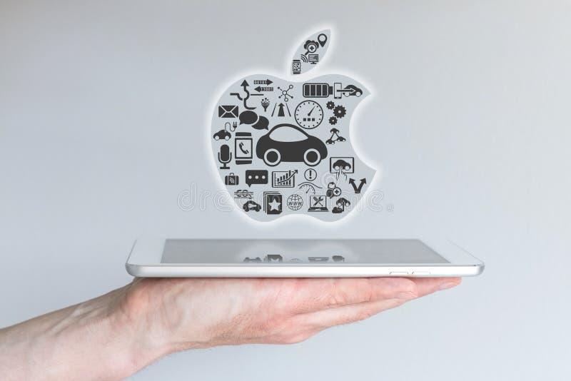 Francfort, Allemagne - 25 octobre 2015 : Main masculine jugeant le comprimé d'iPad avec le concept d'Apple iCar illustration de vecteur