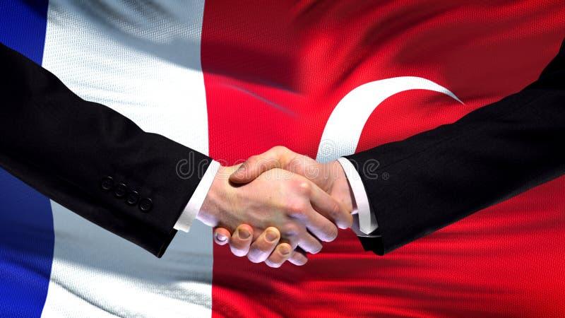 Francja i Turcja uścisk dłoni, międzynarodowi przyjaźni powiązania, chorągwiany tło obrazy royalty free