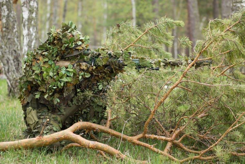 Francotirador camuflado en el bosque fotos de archivo