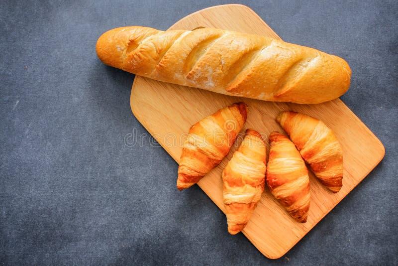 Francuski bochenek i cztery croissants na drewnianej tnącej desce na ciemnym rzemiośle tapetujemy zdjęcia stock