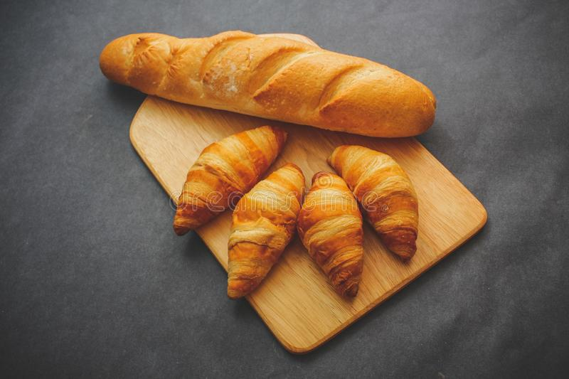 Francuski bochenek i cztery croissants na drewnianej tnącej desce na ciemnym rzemiośle tapetujemy obraz royalty free