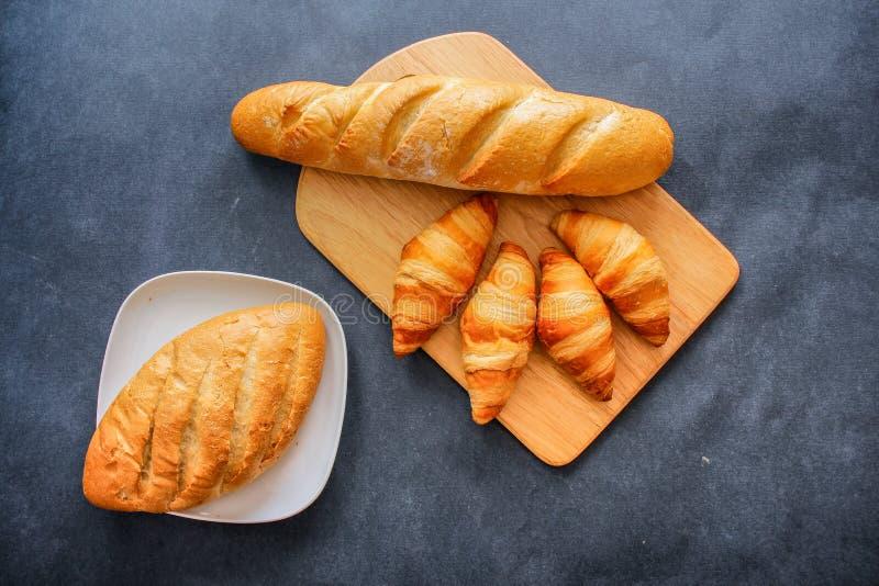Francuski bochenek i cztery croissants na drewnianej tnącej desce na ciemnym rzemiośle tapetujemy fotografia royalty free