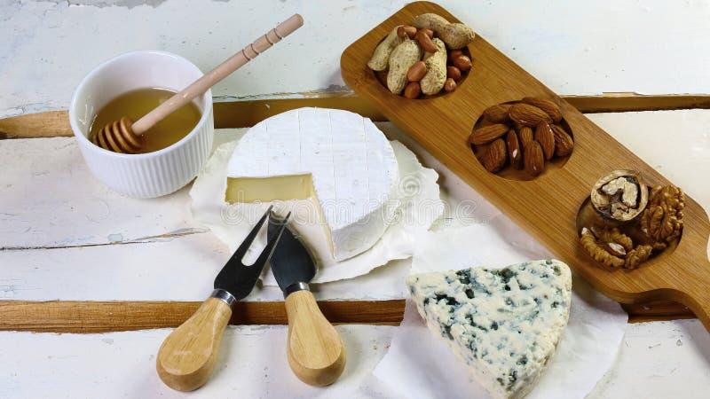 Francuski camambert, ser z błękitnym pleśnieniem z miodowymi i różnorodnymi typ dokrętki na starym stole Mieszkanie nieatutowy zdjęcie stock