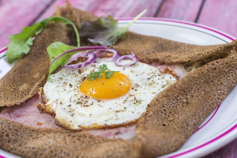 Francuski Gryczany krepdeszynowy galette z baleronem i jajkiem dla smakowitego zdrowego lunchu na różowym drewnianym tle obraz stock
