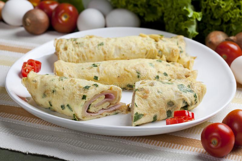 Francuski omelette na tnącej desce Omelette w Francuskim z kraciastym serem i pietruszką na zielonej tnącej desce zdjęcia stock