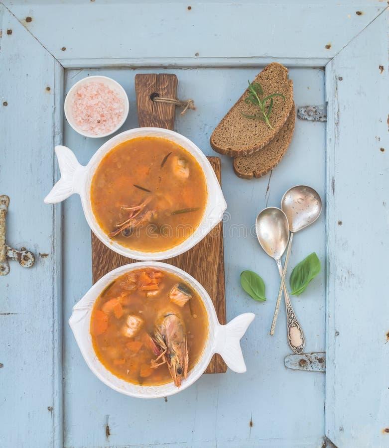 Francuskiej Bouillabaisse ryba pomidorowa polewka z łososiem polędwicowym, garnelą i pikantność na nieociosanej drewnianej desce  zdjęcie royalty free