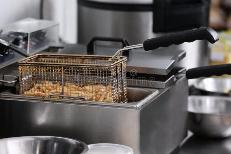 Francuzów dłoniaki w głębokim fryer na kuchni zdjęcie stock