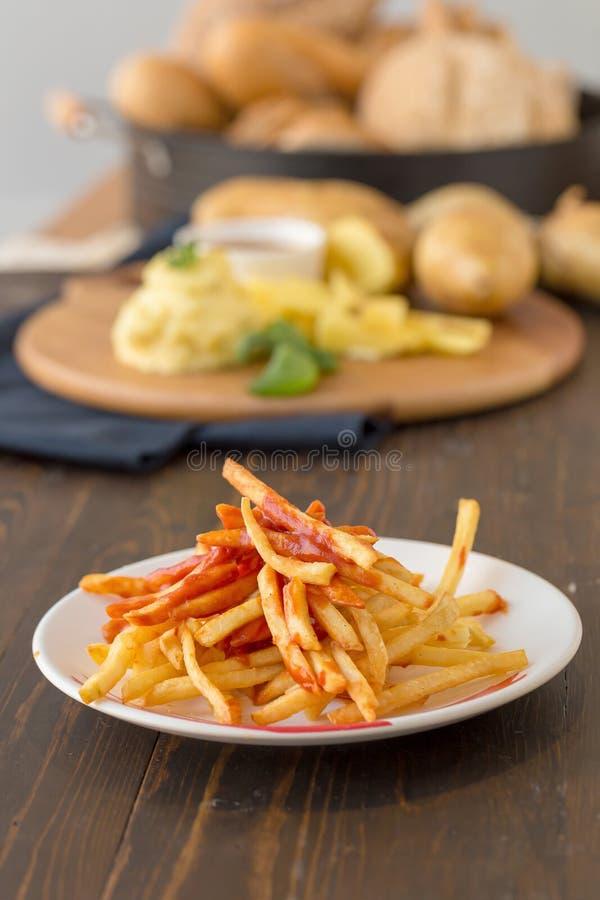 Francuzów dłoniaki z ketchupem na drewnianym tle zdjęcia stock