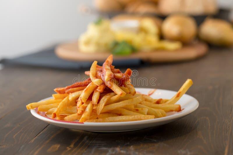 Francuzów dłoniaki z ketchupem na drewnianym tle fotografia stock