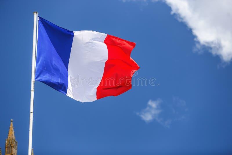 Francuz flaga przeciw błękitnemu chmurnemu niebu fotografia stock