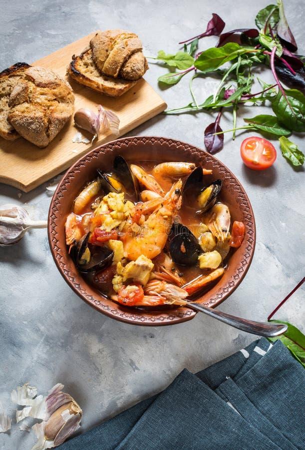 Francuza rybi zupny Bouillabaisse z owoce morza krewetkowym, łosoś polędwicowy, mussels na betonowym tle fotografia royalty free