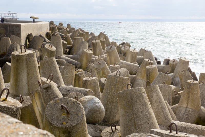 Frangiflutti concreti accatastati sulla spiaggia fotografie stock