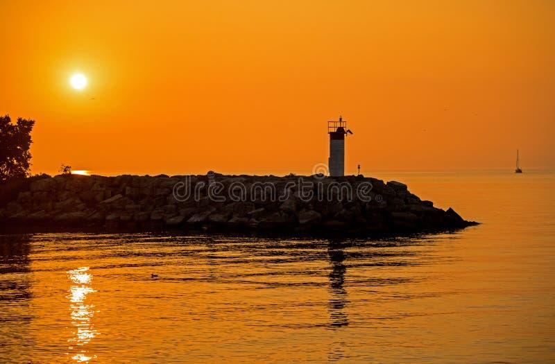 Frangiflutti e faro con il Sun che aumenta sul lago Ontario fotografia stock