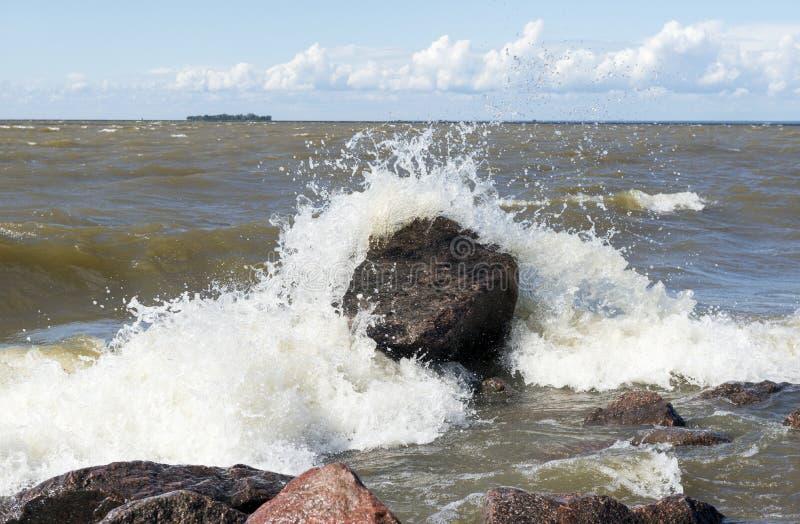 Frangiflutti su una grande roccia, acqua, spruzzo, gocce, spiaggia immagini stock libere da diritti
