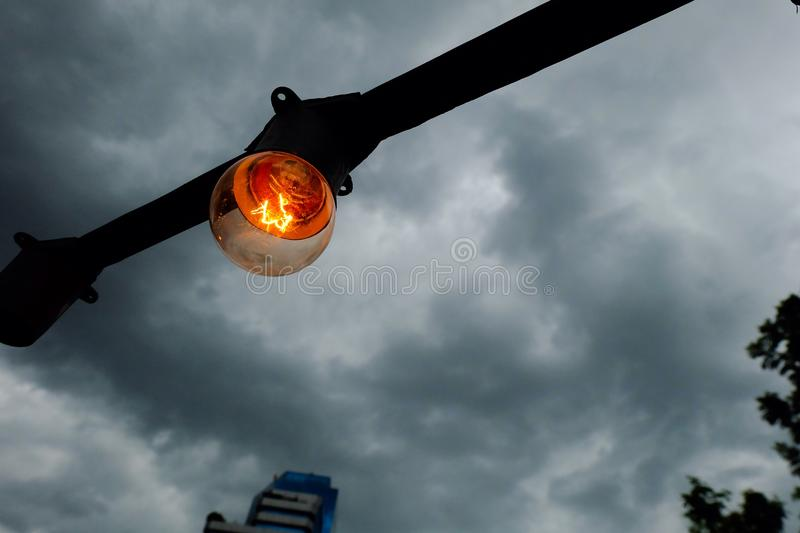 Light bulb in the rain cloud. A light bulb is bright under the rain cloud royalty free stock image