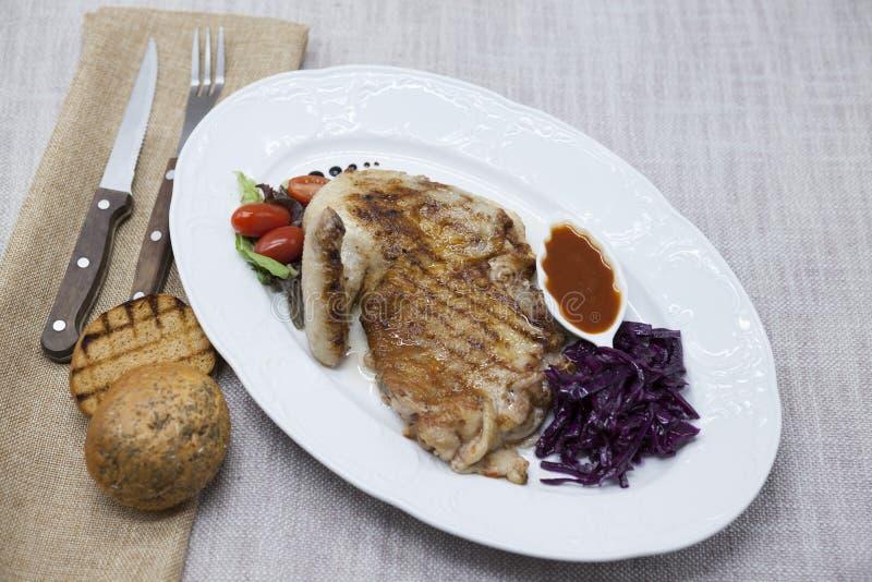 Frango assado suculento com vegetais e ketchup Servido na placa da porcelana em uma toalha de mesa com forquilha e faca Torneira  imagem de stock royalty free