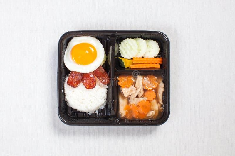 Frango com molho com ovo frito em arroz colocado em uma caixa plástica preta, colocado em uma toalha branca, uma caixa de comida fotos de stock royalty free