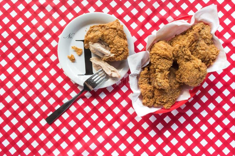 Frango frito na placa com a forquilha na disposição horizontal da toalha de mesa vermelha do tabuleiro de damas imagem de stock
