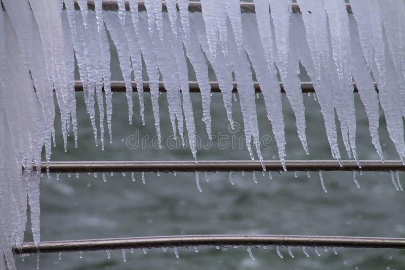 Franja del carámbano en las verjas del metal cerca del mar imagenes de archivo
