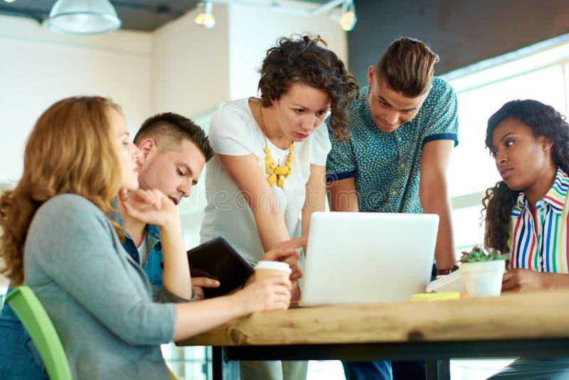 Frank bild av en grupp med lyckat affärsfolk som fångas i ett livligt idékläckningmöte arkivbilder