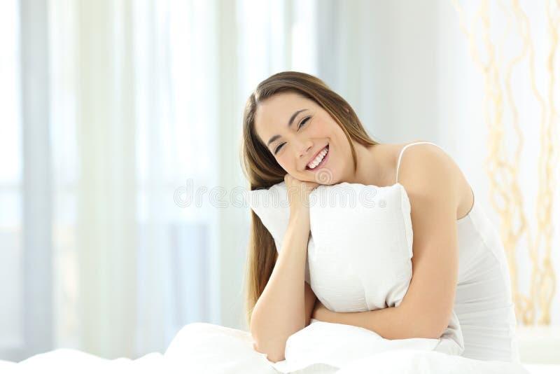 Frank flicka som omfamnar en kudde som ser kameran i sängen royaltyfri bild