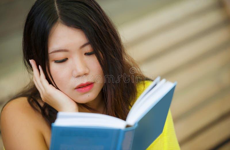 Frank livsstilstående av den unga härliga och avkopplade asiatiska koreanska studentflickan på läseboken eller att studera utomhu royaltyfria bilder