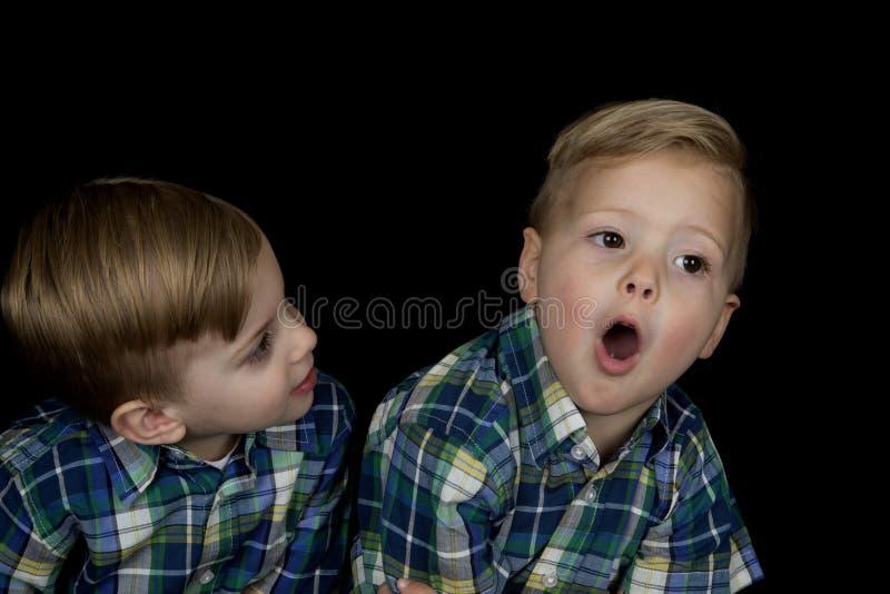 Frank stående av två unga pojkar som bär matcha skjortor royaltyfri bild